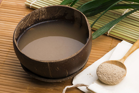 Kava root drink in kava shell and spoon of kava powder